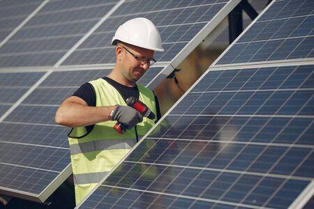 Photo pour Man in a white helmet near a solar panel - image libre de droit
