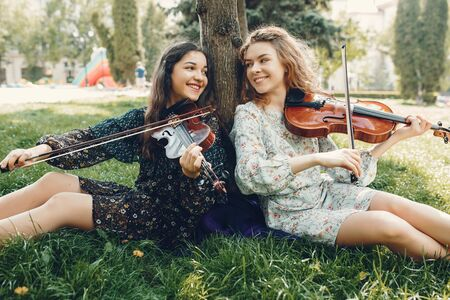 Photo pour Beautiful and romantic girls in a park with a violin - image libre de droit