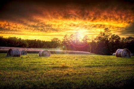 Foto de Beautiful sunset lighting a field with hay rounds producing brilliant and amazing colors. - Imagen libre de derechos