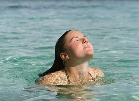 Young woman surfacing from clear green water after a refreshing swim in the tropics.