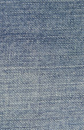 Close up textured background of blue colored jean material.