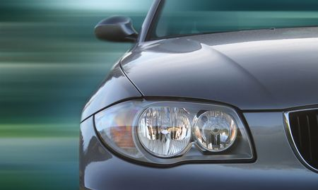 Front of a car with a blurred background. Metallic paint texture on car, not noise. Focus on lights.