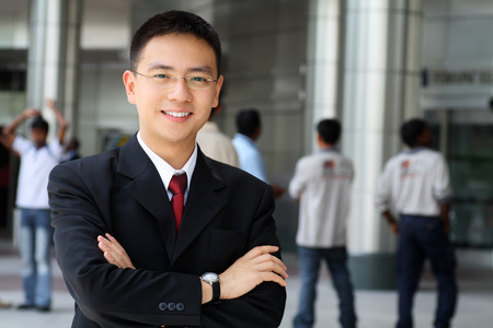 Photo pour Good looking asian business man standing with arms folded. - image libre de droit