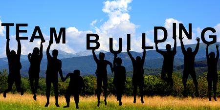 Foto de Silhouettes of people holding letters with TEAM BUILDING at mountains - Imagen libre de derechos