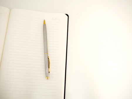 White plain notebook with a pen on white background