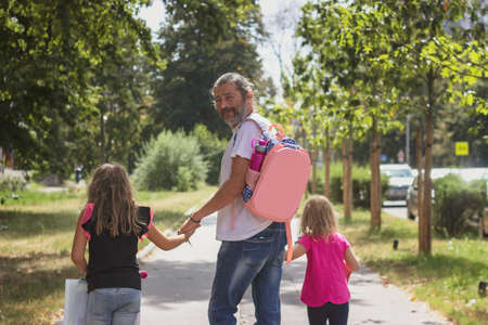Photo pour Father is taking his daughters to school, wearing kids schoolbag on his back - image libre de droit