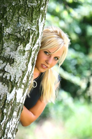 Perfect Blond German Girl behind the tree in nature