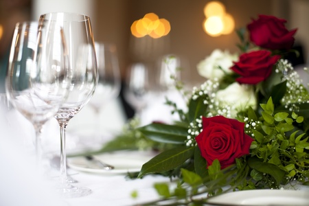 Wedding table decoration rose - Photo shows a nice red rose on a wedding decorated table with soft light in the background and empty glasses. Unfocused you can see sparklne wine glasses.