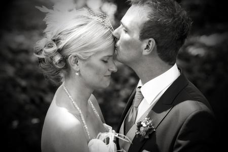 Foto de Very romentic wedding kiss in a parc with a white bride and a dark haired gentlemen as bridgegroom. wedding kiss on forehead - Imagen libre de derechos