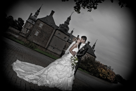 Just married couple in front of castle - artwork   Young couple just married  groom and pretty bride are smiling to the camera  after the wedding ceremony  she is blond and wearing a nice diadem while kissing hot