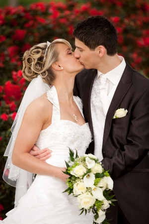 Young couple just married  groom kiss his pretty bride after the wedding ceremony  she is blond and wearing a nice diadem  background red roses and foreground yellow bouquet roses