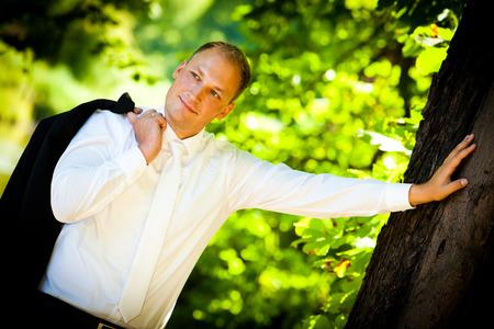 confident groom leaning against tree - groom