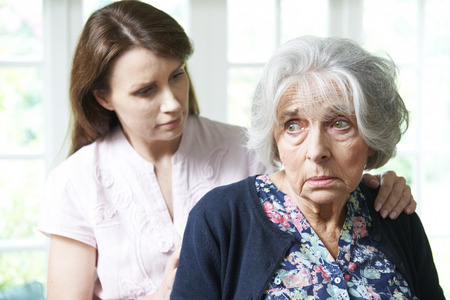 Adult Daughter Consoling Senior Mother At Home