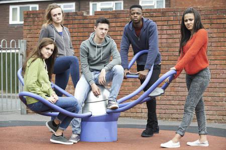 Gang Of Teenagers Hanging Out In Children\'s Playground