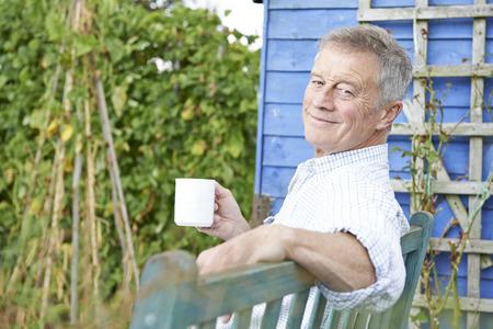 Photo pour Senior Man Relaxing In Garden With Cup Of Coffee - image libre de droit