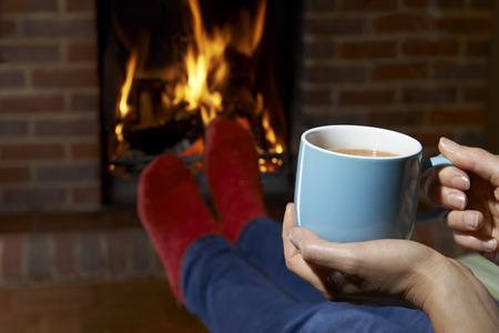 Photo pour Woman With Hot Drink Relaxing By Fire - image libre de droit
