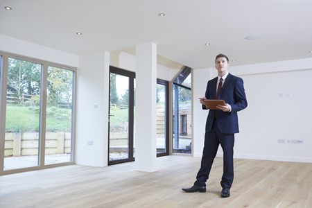Photo for Estate Agent Looking Around Vacant Property For Valuation - Royalty Free Image
