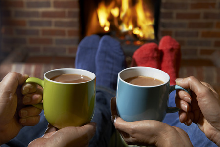 Photo pour Couple With Hot Drink Relaxing By Fire - image libre de droit