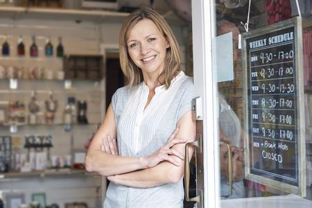 Photo pour Owner Of Gift Shop Standing In Doorway - image libre de droit