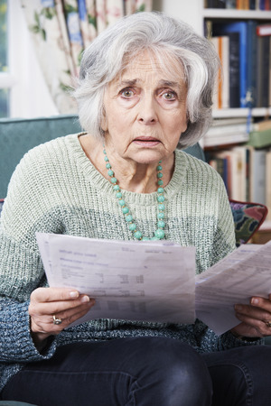 Photo for Senior Woman Going Through Bills And Looking Worried - Royalty Free Image