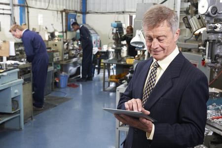 Foto de Owner Of Engineering Factory Using Digital Tablet With Staff In Background - Imagen libre de derechos