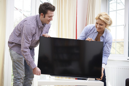 Excited Couple Setting Up New Television At Home