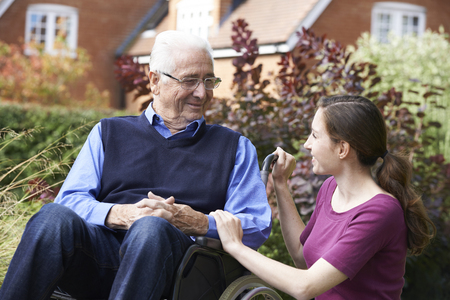 Adult Daughter Visiting Father In Wheelchair