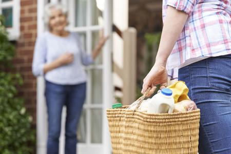 Photo pour Person Doing Shopping For Elderly Neighbour - image libre de droit