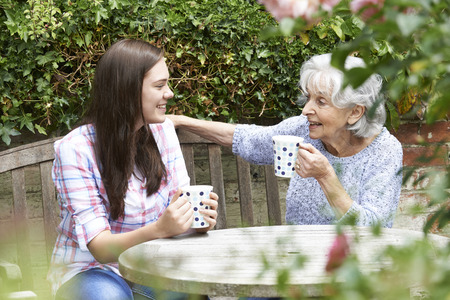 Photo pour Teenage Granddaughter Relaxing With Grandmother In Garden - image libre de droit