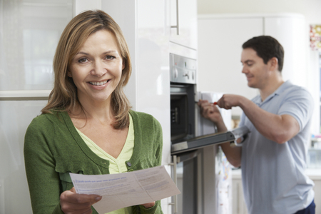 Photo pour Satisfied Female Customer With Oven Repair Bill - image libre de droit