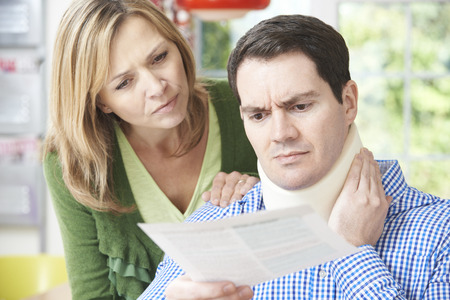 Photo pour Couple Reading Letter In Respect Of Husband's Neck Injury - image libre de droit