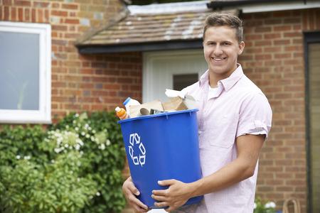 Portrait Of Man Carrying Recycling Bin