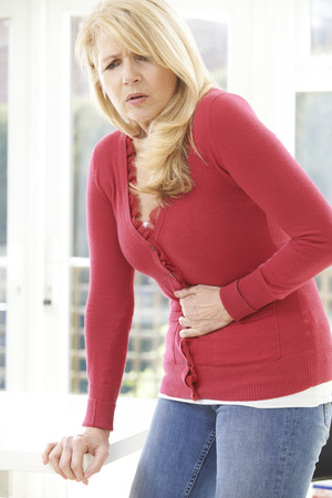 Mature Woman Suffering From Stomach Pain At Home