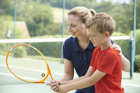 Female Tennis Coach Giving Lesson To Boy