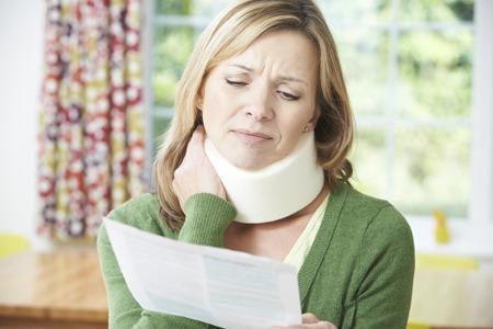 Photo pour Woman Reading Letter After Receiving Neck Injury - image libre de droit