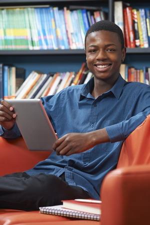 Foto de Male Teenage Student Using Digital Tablet In Library - Imagen libre de derechos