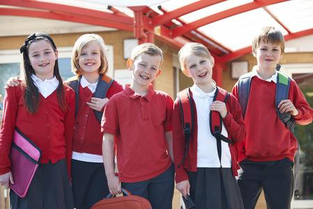 Foto de Portrait Of Schoolchildren Outside Classroom Carrying Bags - Imagen libre de derechos