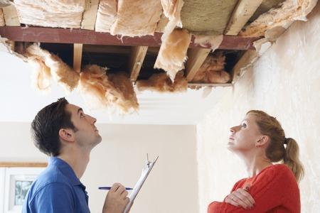 Photo pour Builder And Client Inspecting Roof Damage - image libre de droit