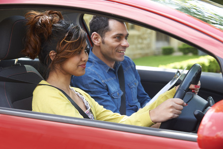 Young Woman Having Driving Lesson With Instructor