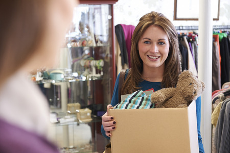 Woman Donating Unwanted Items To Charity Shop