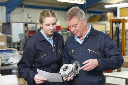 Engineer With Apprentice Looking At Component In Factory