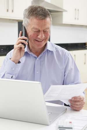Senior Man On Phone Checking Personal Finances