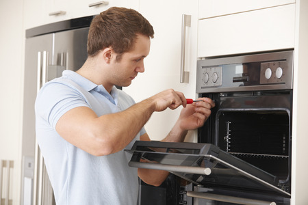 Photo pour Man Repairing Domestic Oven In Kitchen - image libre de droit