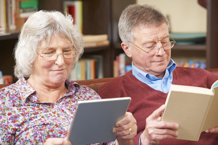 Senior Couple Using Digital Tablet And Reading Book