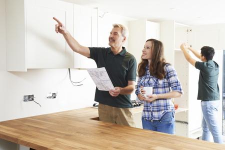 Photo pour Woman With Carpenter Looking At Plans For New Kitchen - image libre de droit