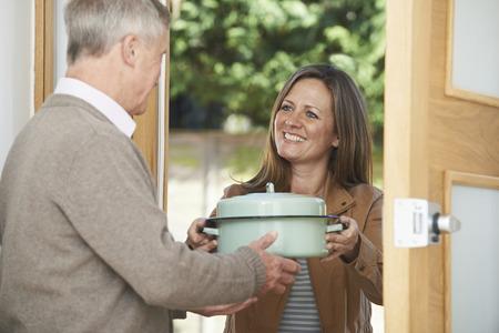 Photo pour Woman Bringing Meal For Elderly Neighbour - image libre de droit