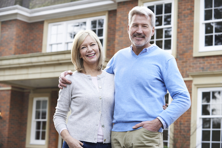 Portrait Of Mature Couple Standing Outside Home