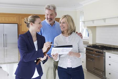 Photo pour Female Realtor Showing Mature Couple Around House For Sale - image libre de droit
