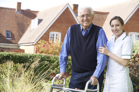 Photo pour Carer Helping Senior Man To Walk In Garden Using Walking Frame - image libre de droit
