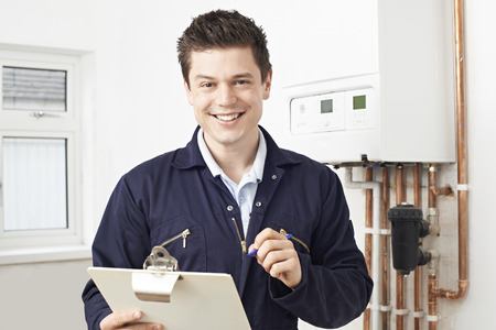 Photo pour Male Plumber Working On Central Heating Boiler - image libre de droit